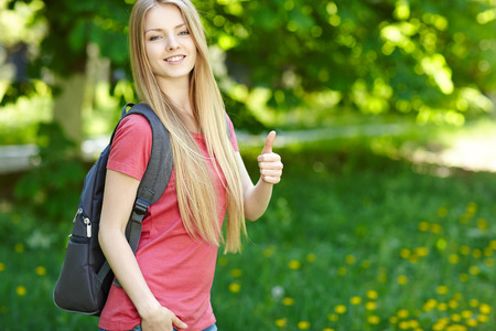 Portrait of young smiling woman outdoors with copy space. Female student with backpack on green background of city park gesturing thumb up. photo