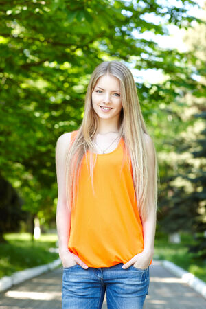 Summer girl portrait.  Casual woman standing with hands in pockets smiling happy on sunny summer or spring day outside in park. Pretty young woman outdoors. photo