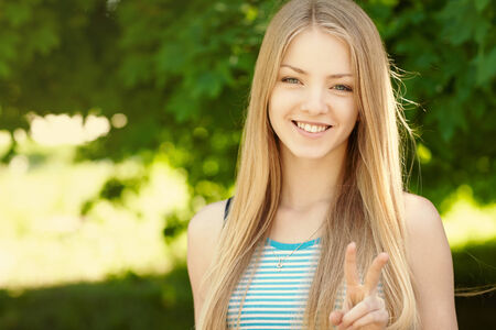 Summer girl portrait.  Closeup of a woman smiling happy on sunny summer or spring day outside in park showing victory or peace sign. Pretty young woman outdoors. photo