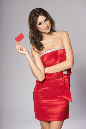 cocktaildress: Beautiful fashion female in red cocktail dress showing red card in hand, over white background Stockfoto