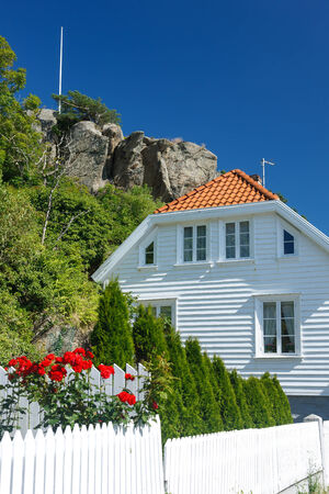 outside of the country: Traditional white wooden house in Norway attached to a mountain, summer day