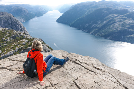Woman sitting on Pulpit Rock  Preikestolen, Norway enjoying Lysefjorden view.  Pulpit rock is a massive cliff 604 metres (1982 feet) above Lysefjorden, almost flat, and is a famous tourist attraction in Norway.