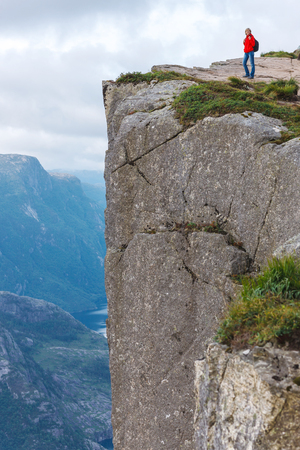 Woman hiker standing on cliff of Pulpit Rock  Preikestolen, Norway. Pulpit rock is a massive cliff 604 metres above Lysefjorden, almost flat, and is a famous tourist attraction in Norway.