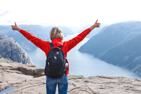 outspread: Back view of happy woman enjoying freedom with arms outspread and gesturing thumbs up on Pulpit Rock  Preikestolen, Norway.  Pulpit rock is a famous tourist attraction in Norway. Stock Photo