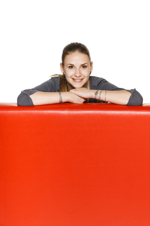 Smiling woman leaning on the red leather couch photo