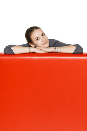 Calm relaxed woman leaning on the red leather couch photo