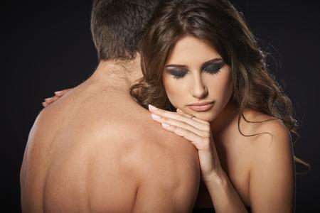 mujer desnuda de espalda: Primer plano de una pareja joven sexy abrazando contra el fondo negro