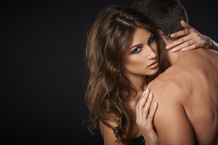 man and woman sex: Closeup of sexy young couple embracing against black background Stock Photo