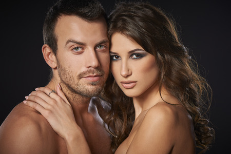 erotic couple: Closeup of sexy young couple embracing against black background Stock Photo