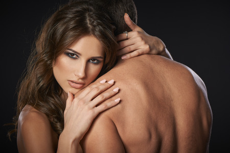 romantic sex: Closeup of sexy young couple embracing against black background Stock Photo