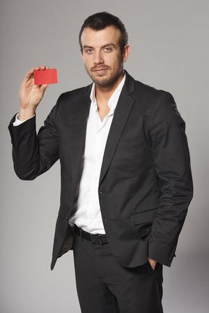 hombre con barba: Retrato de hombre de moda relajada en traje mostrando la tarjeta roja en la mano, contra el fondo gris