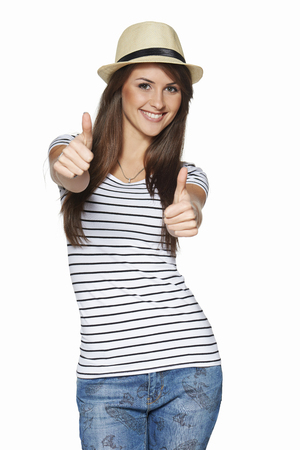 all smiles: Happy excited young woman in striped tshirt and straw hat giving thumbs up, over white  Stock Photo