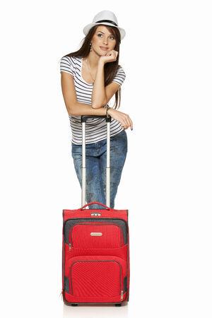 femme valise: Femme touristique. Pleine longueur pensive jeune femme se penchant sur sa valise en détournant les yeux pensée, isolé sur blanc