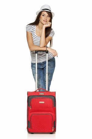 mujer con maleta: Turista de la mujer. Longitud total pensativo mujer joven, apoyado en su maleta mirar lejos pensamiento, aislado en blanco Foto de archivo
