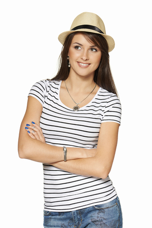 gratified: Smiling young woman in stripped tshirt and straw hat with folded hands looking out of frame, isolated on white background.