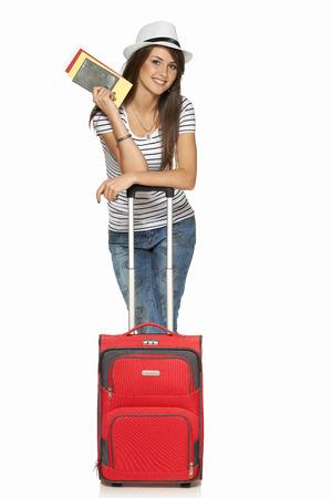 パスポートとチケットは、白い背景で隔離の保持旅行スーツケースとカジュアルな地位で若い女性の完全な長さ