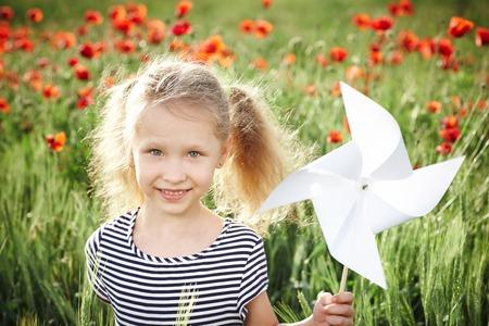 MOLINOS DE VIENTO: Primer plano de la niña sonriente feliz de pie en la pradera de amapola y con molinete de juguete molino de viento blanco