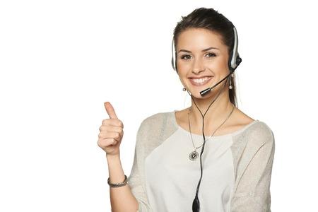 Operador auricular centro de llamadas sonriente mujer haciendo un gesto pulgar hacia arriba, en contra de blancos