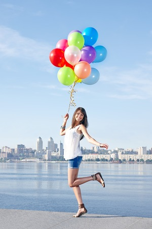 excited woman: Happy young woman with colorful balloons in full length jumping, urban scene, outdoors