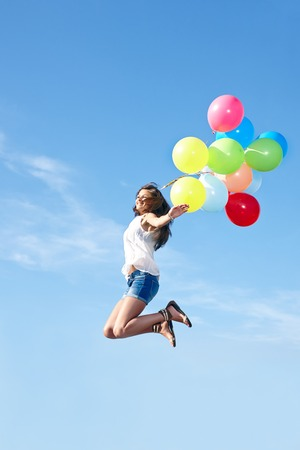 weather balloon: Excited young woman with colorful balloons jumping over blue sky background