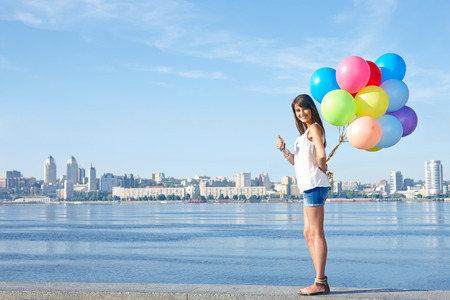 Summer holiday, celebration and present concept: happy young woman holding colorful balloons behind back and gesturing thumb up, standing in full length, city view, outdoors photo