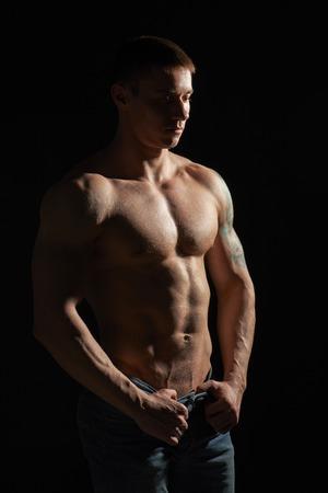 Muscular man posing in studio over black background photo