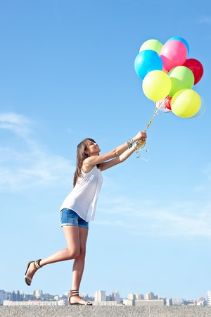 Happy young woman flying away with colorful balloons in full length, urban scene,city view, outdoors photo