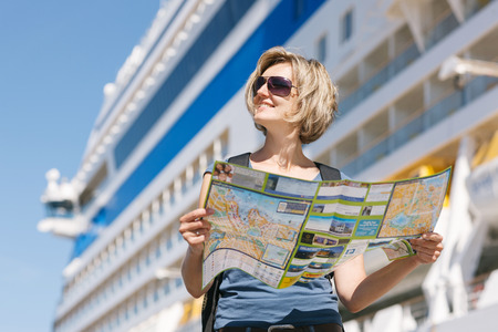Woman tourist on shore with a map, standing in front of big cruise liner, summer day