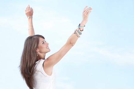 Free happy woman enjoying life with stretched arms against blue sky background photo