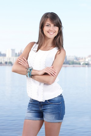 Portrait of smiling young woman, city view, outdoors photo