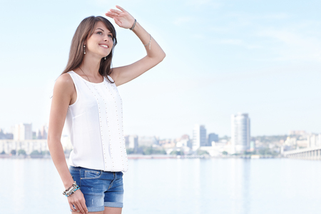 birdwatcher: Smiling young woman searching looking far away, city view, outdoors