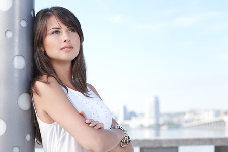 Closeup of thinking young woman outdoors, city urban view photo