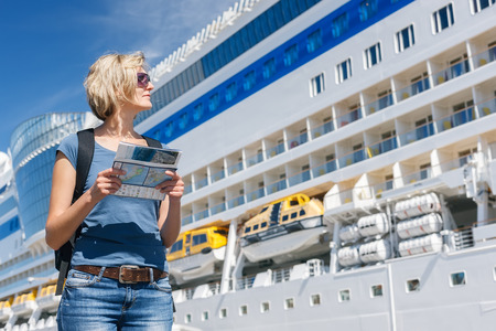 excursion: Woman tourist on shore holding advertising booklet and looking at big cruise liner, summer day