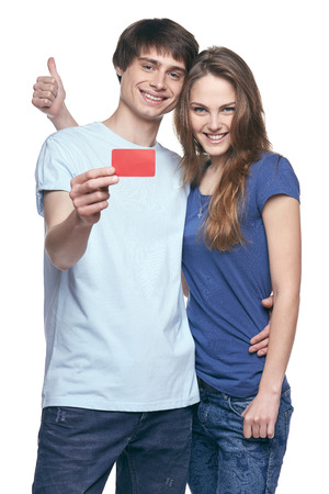 Happy couple in tshirts hugging, man showing blank credit card, woman gesturing thumb up, on white background photo