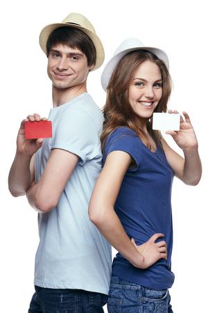 Pareja feliz en las camisetas y los sombreros de paja de pie de espaldas, mostrando las tarjetas de crédito en blanco, sobre fondo blanco Foto de archivo