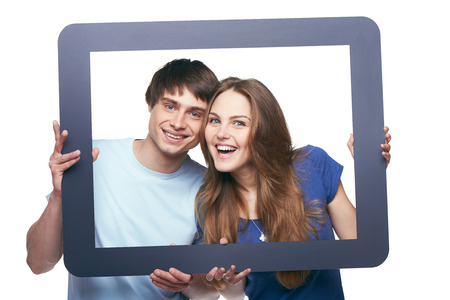 Happy couple looking through tablet frame and smiling at camera, over white background photo
