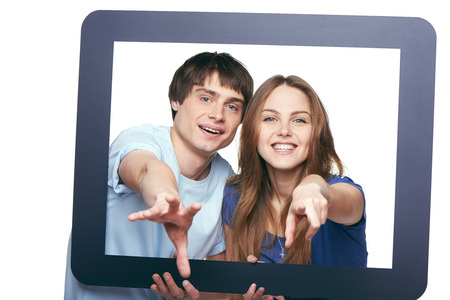Smiling young couple looking through tablet frame and stretching their hands for you, over white background photo