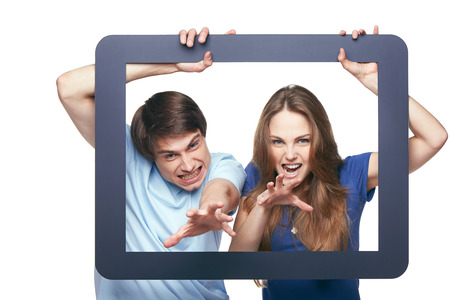 grasp: Funny picture of young couple going to grasp you through tablet frame, over white background