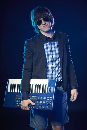 backlit keyboard: Musician standing holding a keyboard