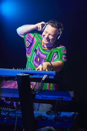 mid age: Happy mid age musician playing on a keyboard at a concert Stock Photo
