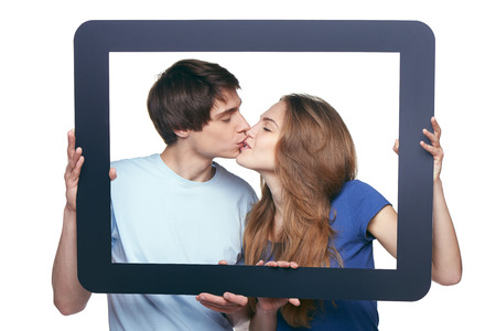 Happy in love couple holding tablet frame and kissing photo