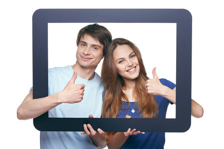 Happy couple looking through tablet frame and giving thumbs up photo