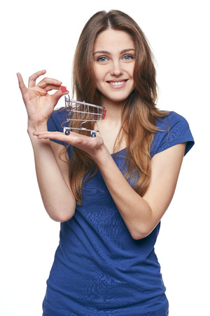 SATISFIED: Shopping concept. Smiling surprised young woman showing small empty supermarket shopping cart on her palm, over white background