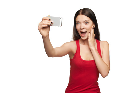 Happy surprised young girl taking pictures of herself through cellphone, over white background photo