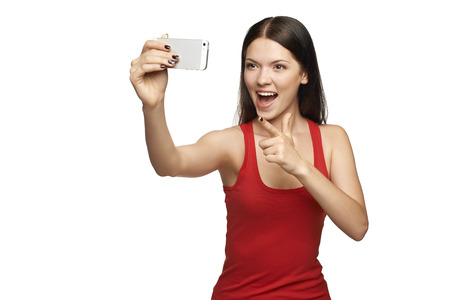 Happy expressive young woman pointing at camera while taking pictures of herself through cellphone, over white background photo