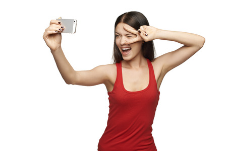 Happy young girl taking pictures of herself through cell phone, over white background photo