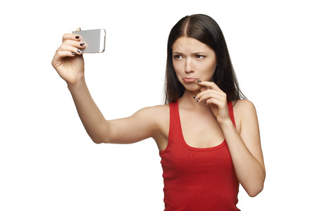 discontent: Young girl pulling discontent face while taking pictures of herself through cellphone, over white background