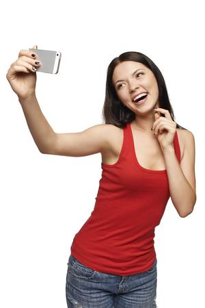 Gelukkig flirten jong meisje het nemen van foto's van zichzelf via de mobiele telefoon, op een witte achtergrond