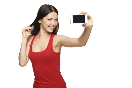 Happy flirting young girl taking pictures of herself through cell phone, over white background photo