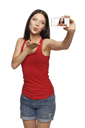 Happy young girl making kiss while taking pictures of herself through cellphone, over white background Standard-Bild